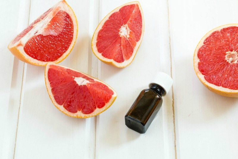 oil essential grapefruit in glass bottle with fresh grapefruit. Spa concept. Selective focus. essence, essential oil, extract, in amber glass bottle with dropper
